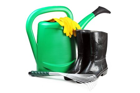 Gardening tools: watering can, rubber boots, rake and yellow  gloves photo