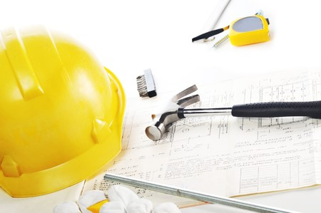 Yellow hardhat,  gloves and  hammer on drawings Stock Photo