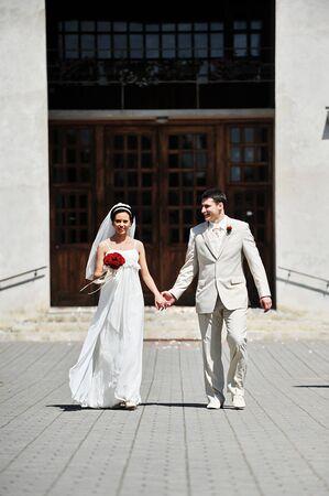 church flower: Newly wed couple  go on sidewalk for church Stock Photo