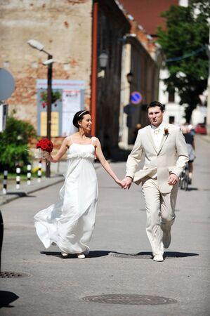 Newly wed couple  run on sidewalk Stock Photo - 7720209