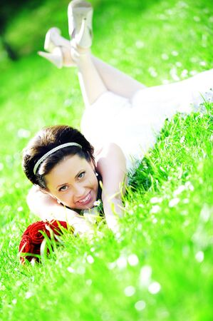 bride in white dress lying down in  grass. Stock Photo - 7683271