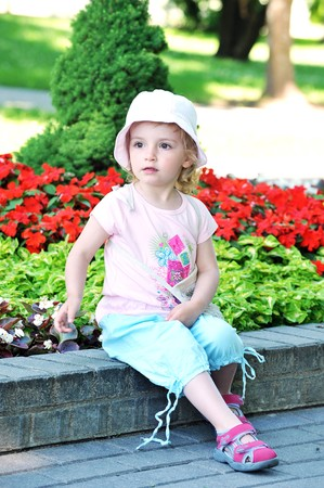 little girl sitting on  park bench photo