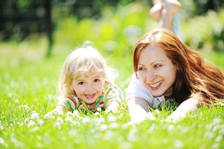 Beautiful young mother with her  daughter lie on grass . summer. Stock Photo - 7720219