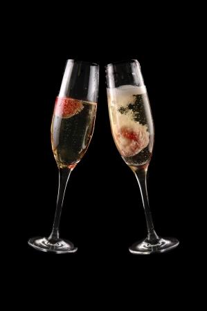 brindis champan: Copa de champagne con fresa sobre fondo negro