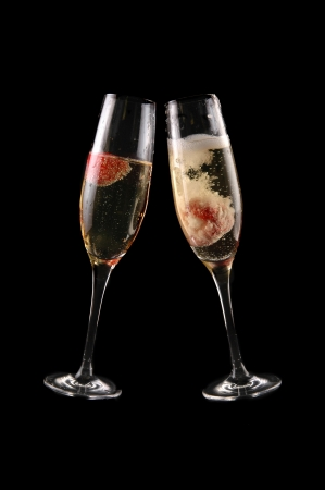 glass of champagne with strawberry on black background photo