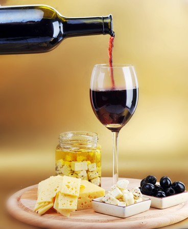 cheese plate: Red wine in wineglass, cheese and olives Stock Photo