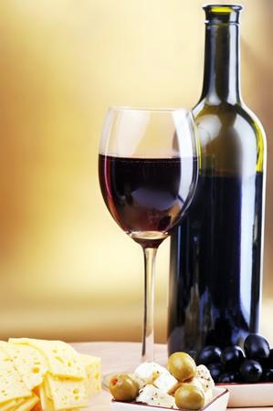 vinos y quesos: botella de vino y queso sobre fondo de oro  Foto de archivo