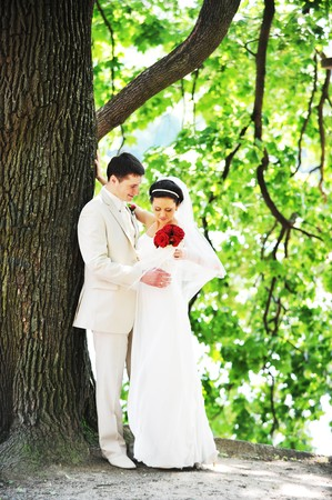 groom and bride in white dress on background of green trees Stock Photo - 7980811