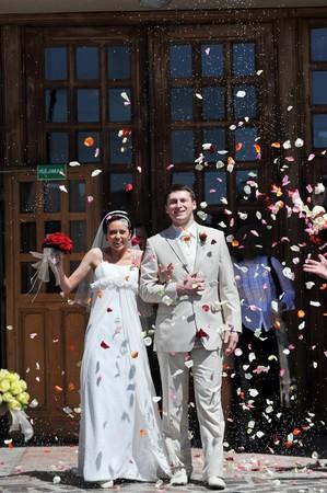 結婚式: バラの花びらのシャワーを浴びている新婚カップル 写真素材