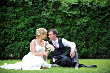 newly-married couple  on green grass in field photo