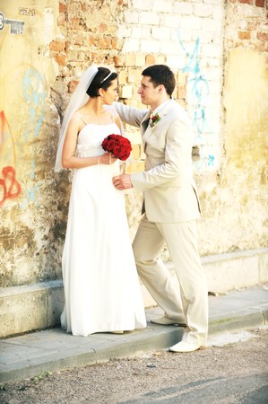 bride and groom stand for an old brick wall Stock Photo - 8015404