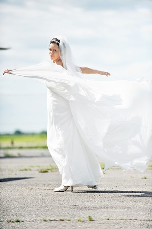 cute bride outside holding hers dress Stock Photo - 10834759