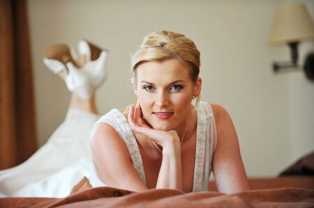 beautiful stylish bride in white dress in room photo