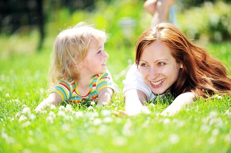 Beautiful young mother with her  daughter lie on grass . summer. Stock Photo
