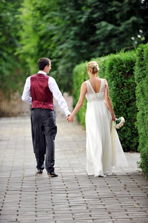 bride and groom walking along the street photo