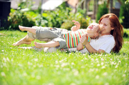 Beautiful young mother with her  daughter playing on grass . summer. photo