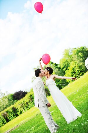groom  and bride  with balloons  on  green field