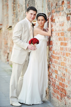 a young old couple: bride and groom  for an old brick wall