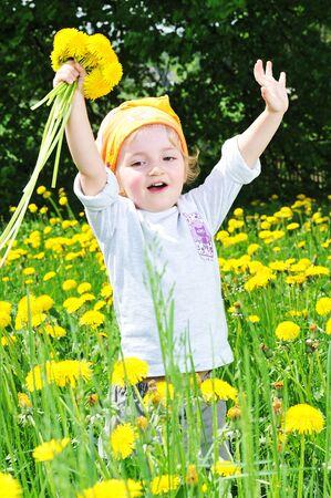 little girl walks on  blossoming field photo