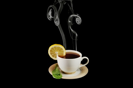 brown cup tea: full cup of tea with lemon and  greens  leaves on  black Stock Photo