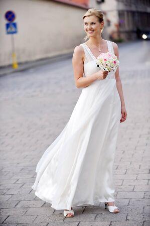 young bride walking on  sidewalk in  urban setting. photo