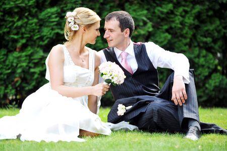 pareja de esposos: pareja de recién casados sobre hierba verde en campo Foto de archivo