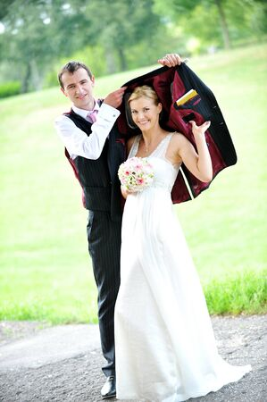 cheerful young pair in  wedding day hides from  rain photo