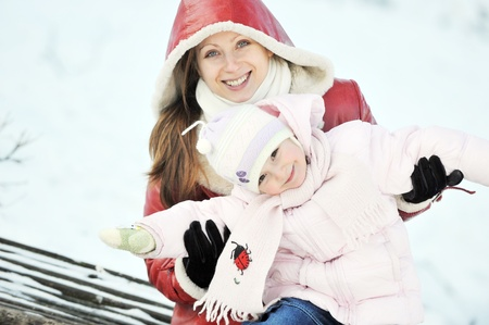 young mother with her daughter sitting on wooden bench in  park. winter day photo