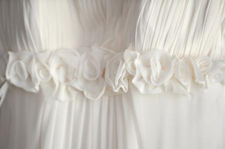 traditional   dress:  white wedding dress hangs on  hanger close up