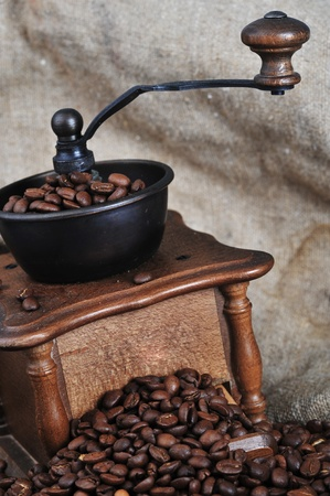 Vintage manual coffee grinder with coffee beans isolated photo