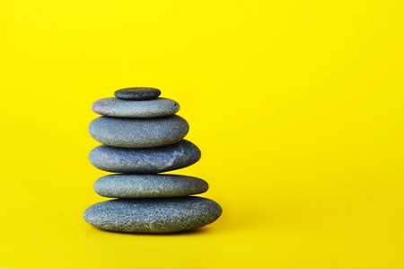 stone tower isolated on yellow background photo