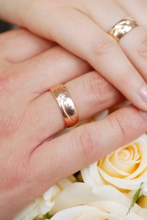 hands with wedding rings on flowers
