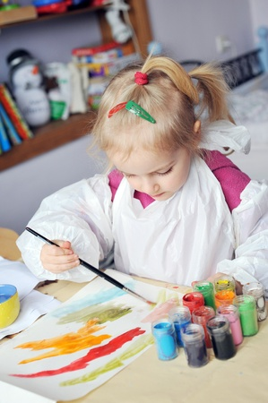 Beautiful little girl is drawing with gouaches on paper Stock Photo - 9316907