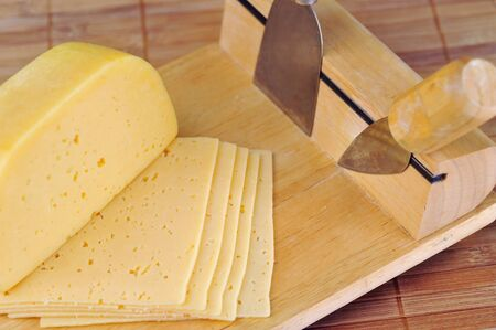 wooden plate and knives for cutting cheese. kitchenware  photo