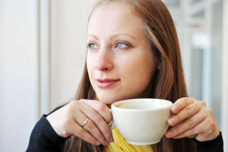 young woman holding  cup of coffee and looking out  window. She drinks coffee at  cafe photo