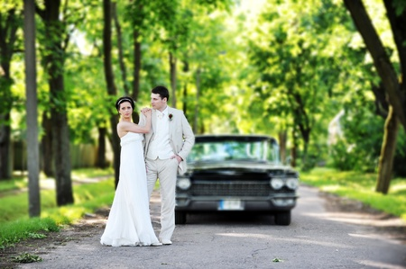 Wedding couple near  car  after their wedding ceremony