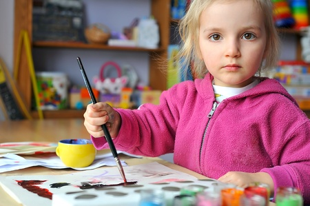 Beautiful little girl is drawing with gouaches on paper Stock Photo