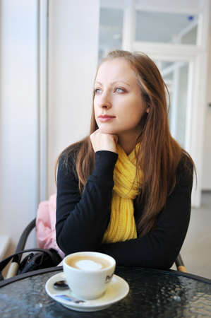 young woman sits at table in cafe. Drinks coffee photo