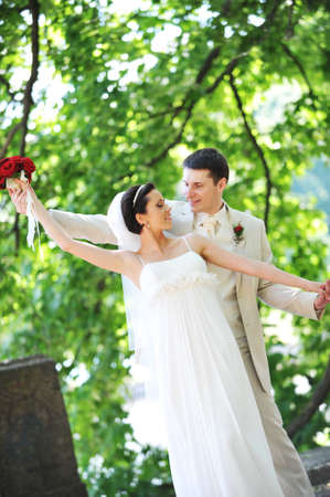 groom and bride in white dress on background of green trees Stock Photo - 9539509