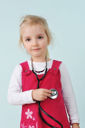 doctor toys: Little girl  holding stethoscope and listens to the heartbeat Stock Photo