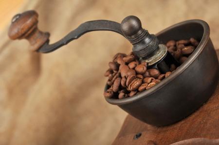 meuleuse: Vintage moulin � caf� manuel avec les grains de caf� isol� Banque d'images