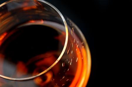 liqueur:  snifter of  brandy in  elegant  glass.  black background