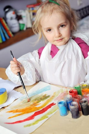 Beautiful little girl is drawing with gouaches on paper Stock Photo - 9721775