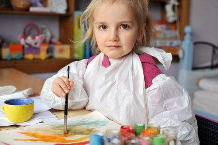 Beautiful little girl is drawing with gouaches on paper Stock Photo - 9808959