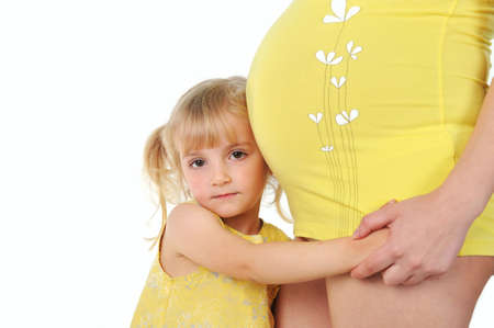 Adorable girl hugging belly pregnant mom's Stock Photo - 9808890