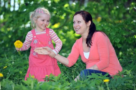 mother and daughter playing  on grass. spring day photo