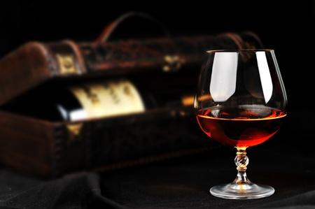 wooden lid: elegant  glass of cognac and bottle in wooden case  background
