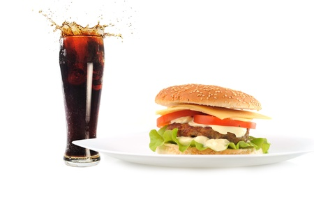 hamburger with cutlet and vegetables on dish with fresh sparking drink photo