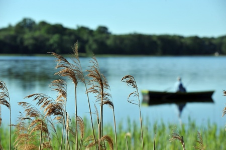 canoe paddle: fisherman in  boat in summer day. fishing on  lake