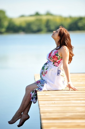 woman sitting  at   jetty. summers day on lakeside Stock Photo